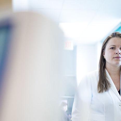 Jessica Beard wearing her white coat inside her medical clinic