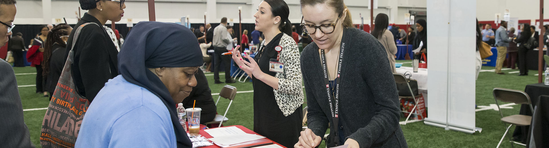 Two women speak to each other at a Temple job fair table.