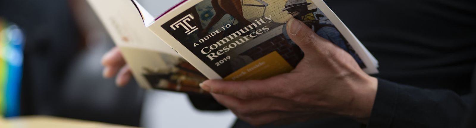 A community member studies a Temple guide to community resources.