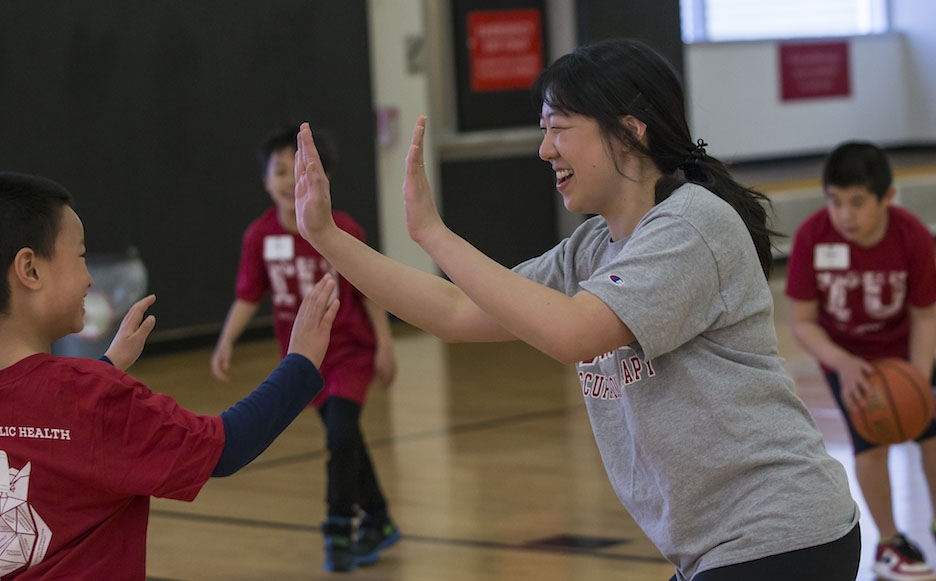 Student working with young learners in basketball clinic